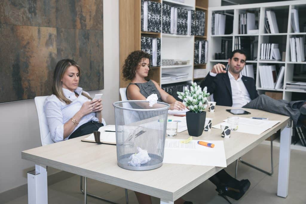 Portrait of three colleagues are boring at table in office and businessman throwing paper in basket
